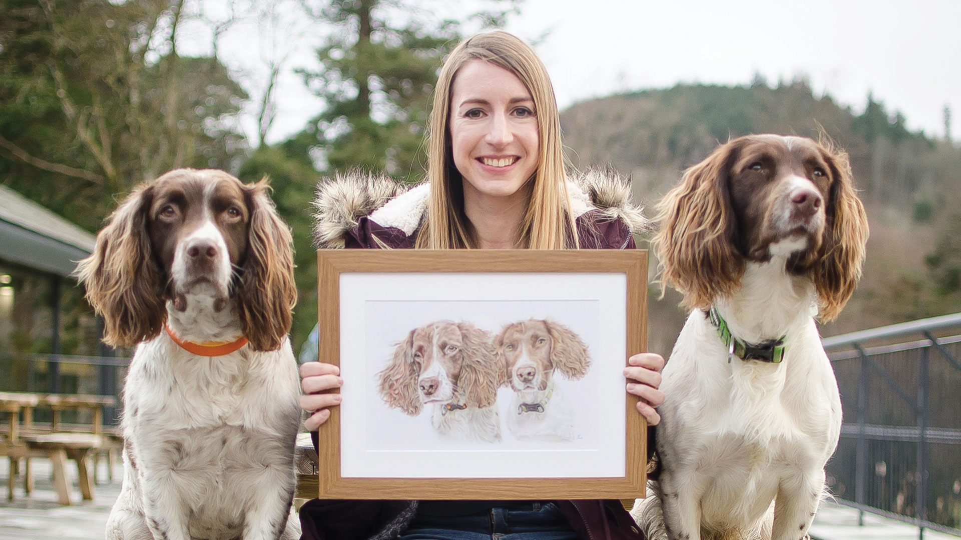 Jess Pritchard, sat between Max & Paddy holding the portrait she drew of them